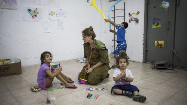 """""""Indiscriminate attacks"""": Israeli children sit in a bomb shelter in Ashkelon during the 2014 Israel-Gaza conflict."""