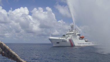 Tensions: A Chinese Coast Guard vessel sprays a water cannon at Filipino fishermen near Scarborough Shoal last year.