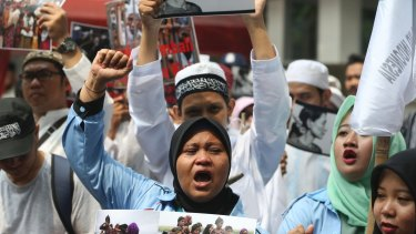Indonesian activists hold poster during a protest in front of the Myanmar Embassy in Jakarta, Indonesia.