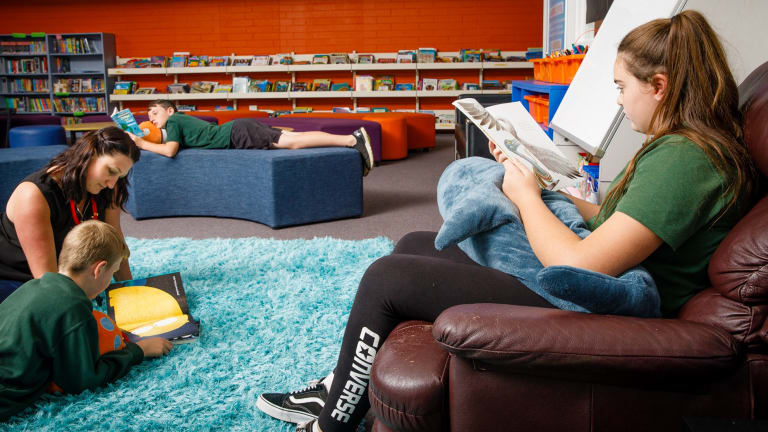 Charnwood Dunlop primary school librarian Bridgette Manley reads with sixth graders Tyreece Ryan (11), Cameron Morton (10), and Trista Buckley (11). The school says employed a teacher-librarian to help lift literacy levels.