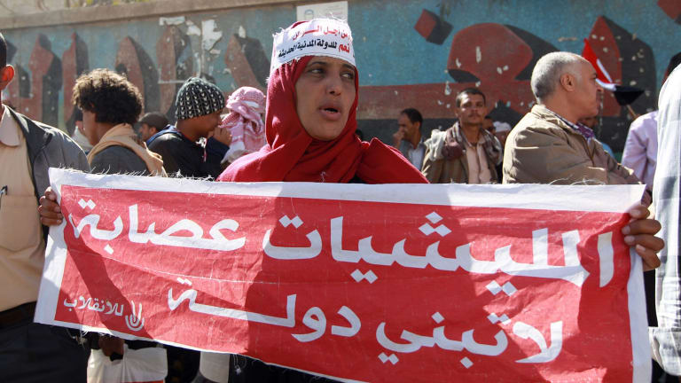 """Yemenis shout slogans during a rally against the occupation of the capital by the Shiite Houthi movement. The woman's sign reads """"militias are gangs that won't build a nation""""."""