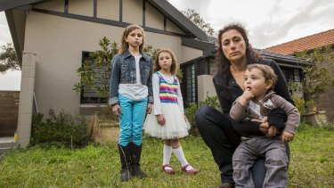 Dana Nehal Joab in front of her house - which she may lose - with her children Hannah, 9, Jennah, 5, and Noah, 17 months.