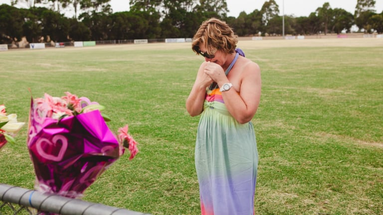 Luke Batty's mother, Rosie Batty, at Tyabb oval reading cards well wishers left following the death of her son in early 2014.
