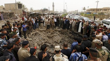 Residents and Iraqi security forces gather around a hole caused by a suicide car attack at a market in Khan Bani Saad, north-east of Baghdad, on Friday. .