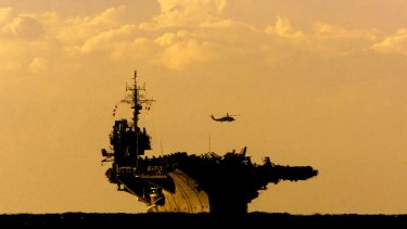 A helicopter hovers above US aircraft carrier USS Kitty Hawk as it enters Sydney Harbour.