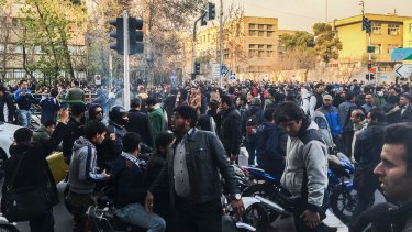 In this photo taken by an individual not employed by the Associated Press, demonstrators gather to protest against Iran's weak economy in Tehran.