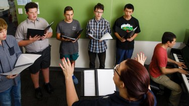 Conductor Rachel Campbell leads members of the Changing Voices choir through a set of vocal exercises. Standing L-R: Tommy Warburton, Oliver Campbell, Caleb Vickers, Ryu Callaway, and Wallace Tan. Accompanying on piano is Lucus Allerton.