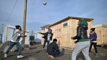 """Migrants play handball in the camp known as the """"New Jungle"""" in Calais on December 3."""