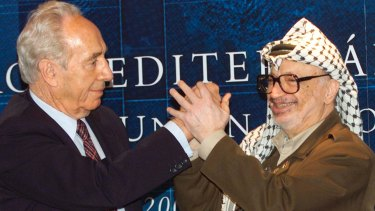 Palestinian leader Yasser Arafat, right, clasps hands with then Israeli Foreign Minister Shimon Peres, left, at a special session of the Euro Mediterranean Project in 2001.