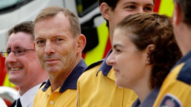 Prime Minister Tony Abbott prepares to receive a medal for 10 years of voluntary service to fire-fighting