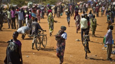 Displaced people walk in a UN compound home to thousands of people displaced by fighting, in Juba, South Sudan in 2013.