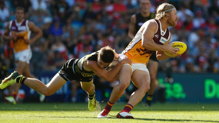 Richmond's Liam Baker tackles the Lions' Daniel Rich.