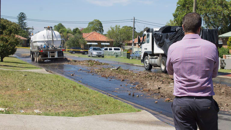 Council workers look on as illegally dumped waste is removed from a Chester Hill street.