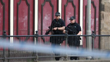 Armed police patrol the streets of Manchester the morning after the bombing.