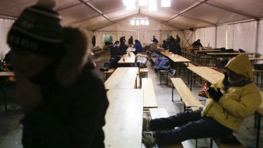 Refugeess warm themselves inside a waiting tent on a cold and snowy early morning, at the central registration center for refugees and asylum seekers in Berlin on Wednesday.