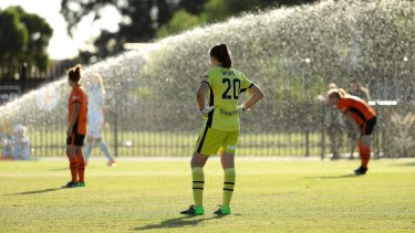 Players look on after sprinklers were turned on during the W-League match between Melbourne City and Brisbane Roar in Fawkner.