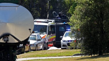 A body covered with a white sheet lies near the corner of Stennett and Heald roads, Ingleburn.