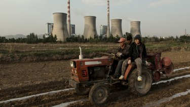 Farmers work in corn fields near the Shantou coal power plant in Shuozhou, China, in April 2014.