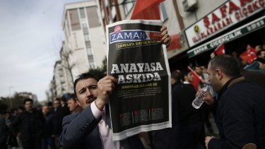 """A man holds Saturday's copy of the newspaper which reads """"the constitution suspended"""" as people gathered in support outside the headquarters of Zaman newspaper in Istanbul, on Sunday."""