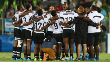 Fiji players and staff huddle together in celebration after winning the rugby sevens.