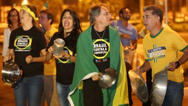 Members of the Brazil's Movement Against Corruption bang on pots and pans in protest against President Dilma Rousseff, during her televised speech.