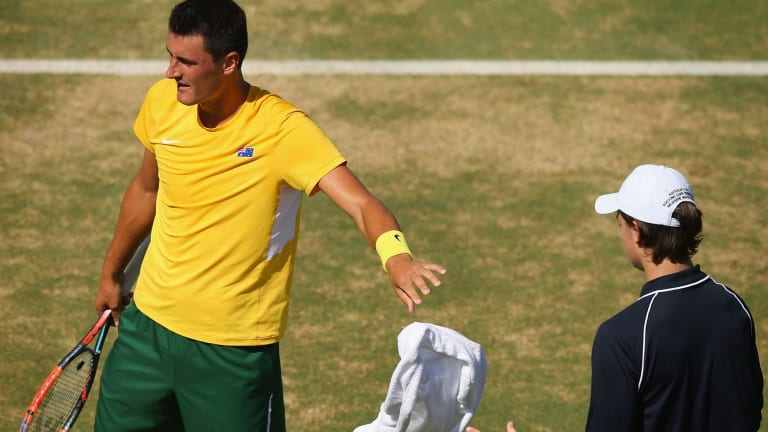 Tough day: Bernard Tomic throws his towel back during his Davis Cup loss to John Isner.