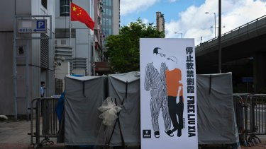 A banner displaying a sketch of late Chinese Nobel Peace laureate Liu Xiaobo and his wife Liu Xia is displayed outside the Chinese liaison office in Hong Kong.