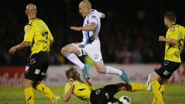 Three strikes: Aaron Mooy of Melbourne City leaps over Jack Petrie of Heidelberg United during the FFA Cup quarter-final on Tuesday.