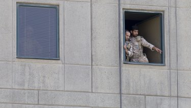 Men in military uniform stand at a window in the Iranian Parliament building.