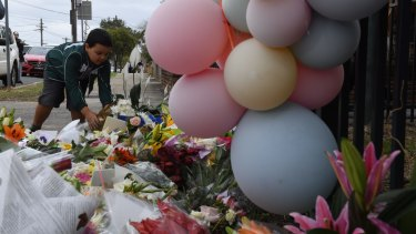 A young boy places flowers outside Banksia Road Public School in Greenacre where two boys were killed.