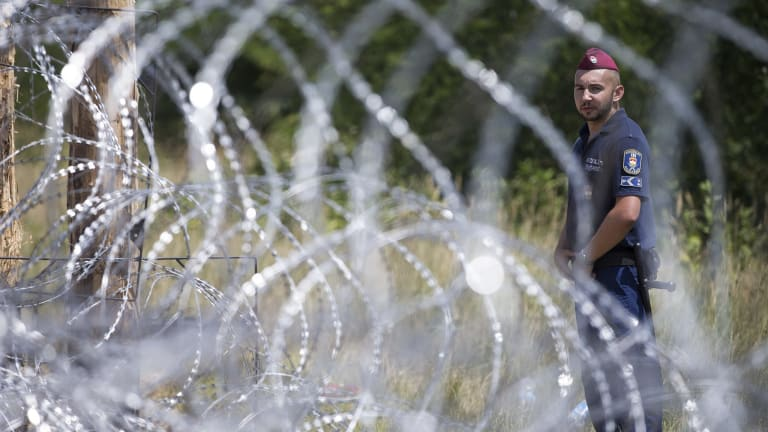 A Hungarian soldier stands next to the first portion of a fence the Hungarian military is erecting on its border with Serbia.