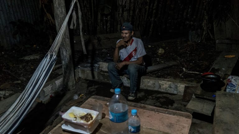 Garcia sits outside his shack in Intuto, Peru. He has been working with academics to preserve records of his language.