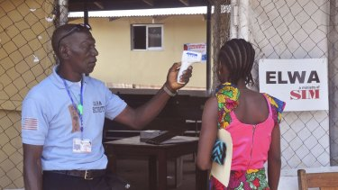 A family member of a boy who contracted Ebola has her temperature measured by a health worker before entering the Ebola clinic in Monrovia, Liberia, were the child is being treated.