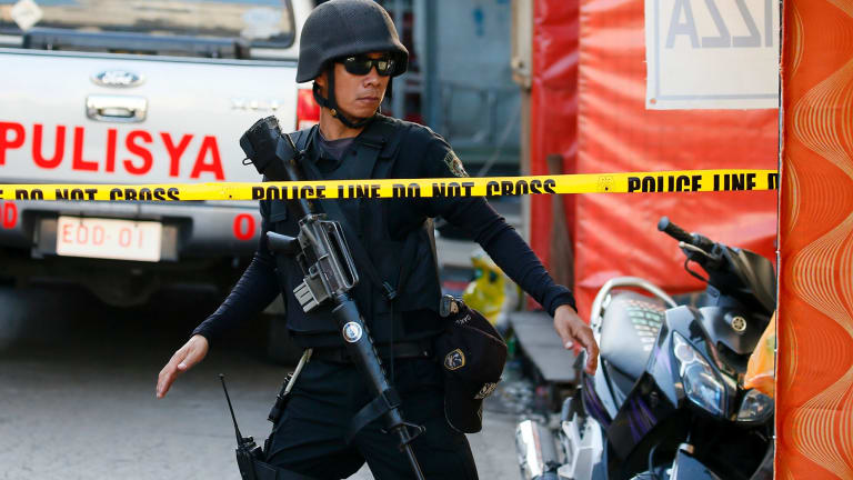 A member of the Philippine National Police secures the area following two overnight explosions in Manila's Quiapo district.