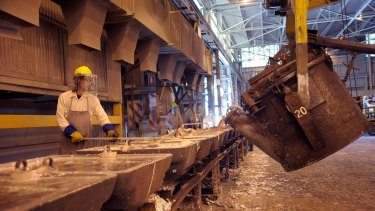 A giant kettle pours molten aluminum into moulds at an Alumina smelting plant.
