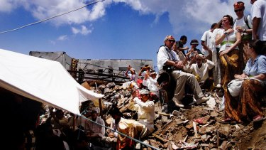 Family and friends of the victims of the 2002 Bali bombing sit amongst the rubble of the Sari club  during a Hindu  cleansing ceremony in November 2002.