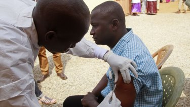 A health worker injects a man with an experimental Ebola vaccine in Guinea in March 2015.