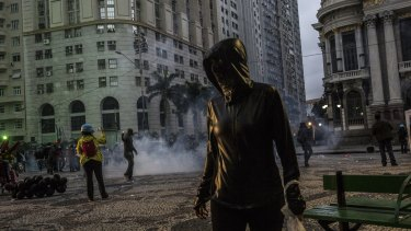 Protesters move away from tear gas during a general strike in Rio de Janeiro, Brazil, on Friday.