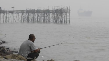 A man fishes near a wooden jetty shrouded in haze in Port Klang, outside Kuala Lumpur, Malaysia.