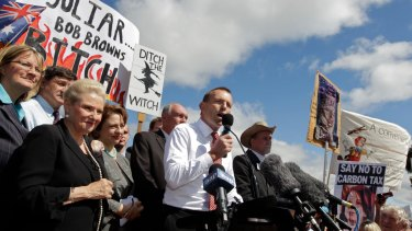 Tony Abbott as opposition leader in front of posters at a ant-carbon tax rally.