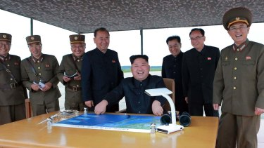 Kim Jong-un, centre, smiles at the site of the test launch of a Hwasong-12 intermediate range missile in Pyongyang on Tuesday in this photo distributed by the regime's news agency.