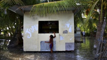 A child wades through sludge and water on the Island Republic of Kiribati in the Central Pacific Ocean.