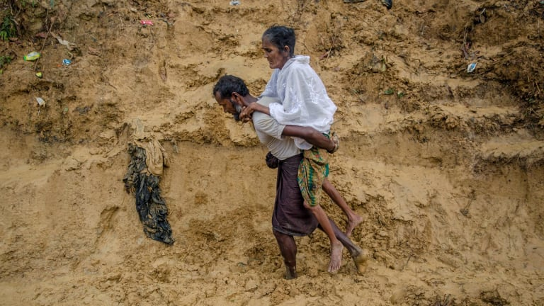 Alishaan, a recently arrived Rohingya Muslim man, carries his sick mother Aishya Khatoon to a hospital at Taiy Khali refugee camp in Bangladesh on Thursday.