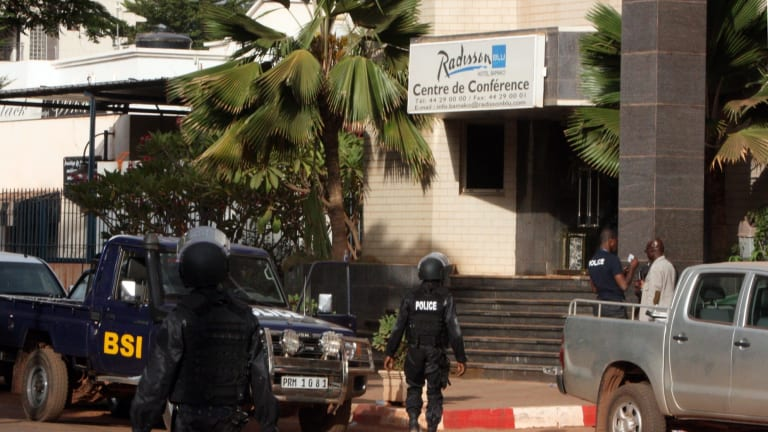 Mali police walk outside an entrance to the Radisson Blu hotel's conference centre after the terrorist attack on Friday.