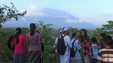 Residents watch smoke coming from the volcano earlier this week.