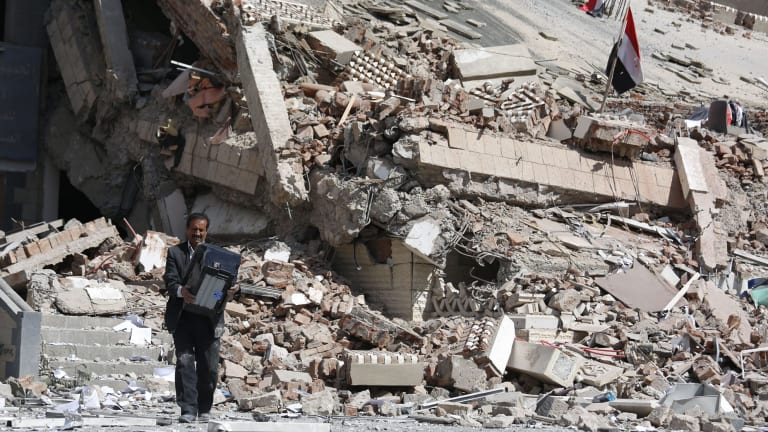 An employee carries a printer out of the Chamber of Trade and Industry headquarters after it was hit by a Saudi-led air strike in Sanaa, Yemen, in January.