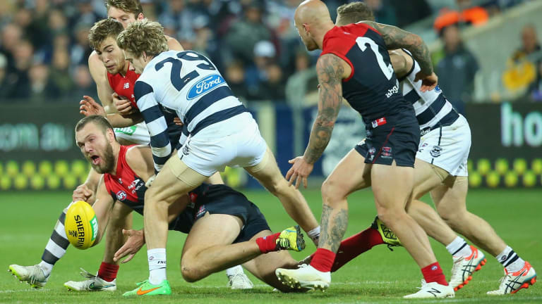 Max Gawn of the Demons handballs as he is tackled by Cameron Guthrie of the Cats at Simonds Stadium on Sunday.