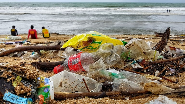 Bali's iconic surf beach in Kuta littered with Coke bottles, thongs, crumpled plastic water cups and drinking straws.