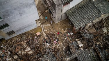 A birds eye view of residents walking past the damaged stores in the aftermath.