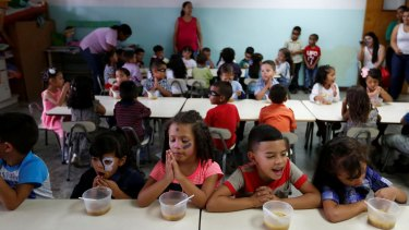 Students pray before a meal of soup cooked for them during an activity for the end of the school year at the Padre Jose Maria Velaz school in Caracas, Venezuela this month.